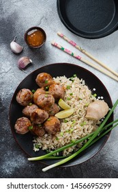 Fried pork meatballs and rice cooked in chinese style, top view on a grey stone background