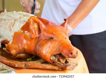 Fried pork on table. Waiter cut whole pork. Traditional dish whole roasted pig with head. Delicious meat barbecue. Roasted pork for serving. Fresh juicy pork meat for lunch. Spanish jamon
