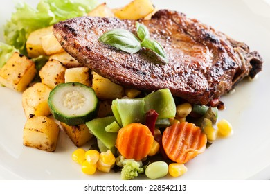 Fried pork with roasted potatoes and vegetables salad