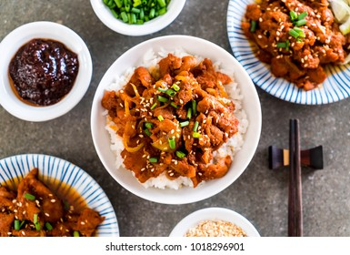 fried pork with spicy korean sauce (bulgogi) on top rice - korean food style