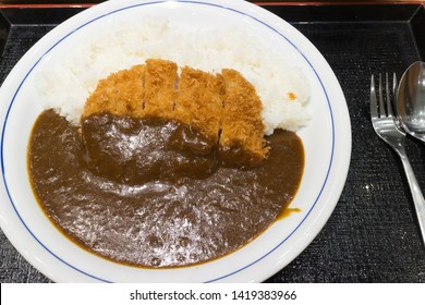 Fried pork Tonkatsu with curry on rice,  white dish and cutlery