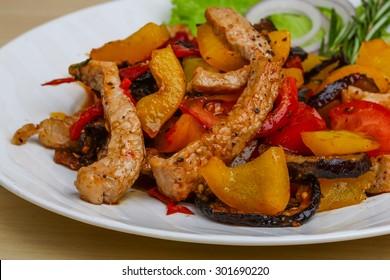 Fried pork with vegetables - tomato, pepper, eggplant