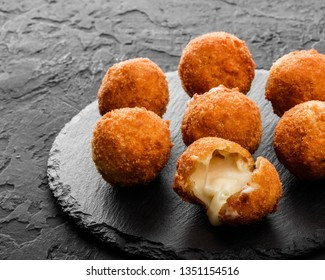 Fried potato cheese balls or croquettes with spices on black plate over dark stone background. Unhealthy food, top view