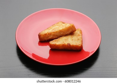 Fried potato croquettes on red plate