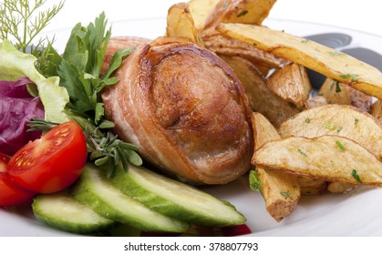 fried potato and meat with vegetables and herbs on the plate