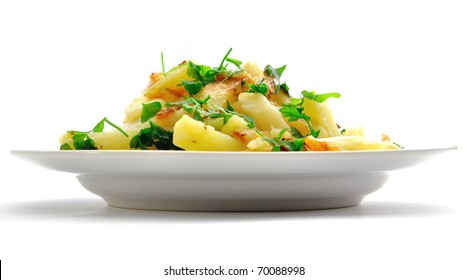 Fried potato on a plate with greens; it is isolated on a white background