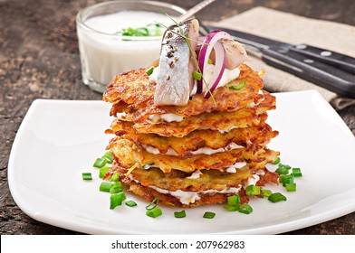 Fried potato pancakes with herring on the old wooden background