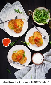 Fried potato pancakes with red caviar and sour cream, fritter, roesti. Traditional delicious food, lunch. Top view, flat lay