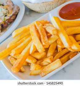 Fried Potato in white dish with tamato sauce