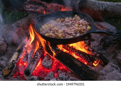 fried potatoes with bacon and onions on iron cast pan as  campfire cooking recipes