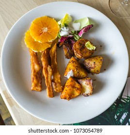 Fried potatoes and batats on served on a dish in a restaurant