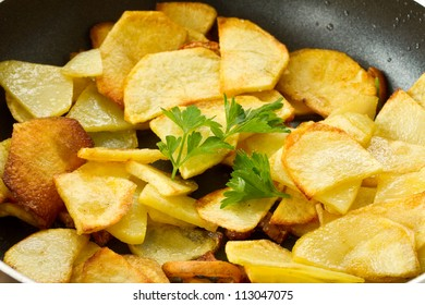fried potatoes in a frying pan on a wooden board