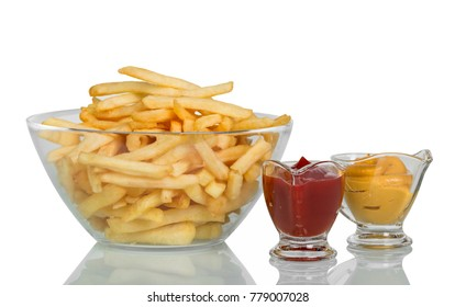 Fried potatoes in large glass bowl, ketchup and mustard isolated on white background