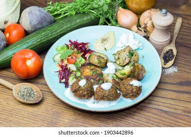 Fried potatoes with meatballs and vegetable, served on a light blue plate. Food decoration in background.