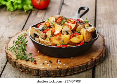 Fried potatoes with mushrooms in a frying pan
