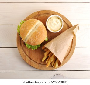 fried potatoes in a paper bag, cheese sauce and hamburger on wooden background - top view