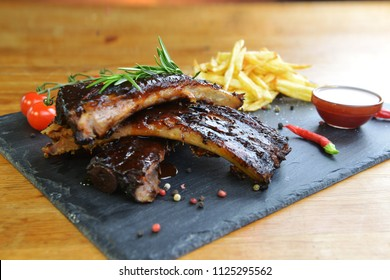 fried potatoes and pork ribs on aplate
