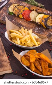 Fried potatoes in a rural and French fries, vegetables on coals