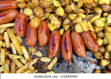 Fried potatoes with fried sausages on frying pan.