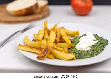 Fried potatoes with spinach on the plate with bread in the background.