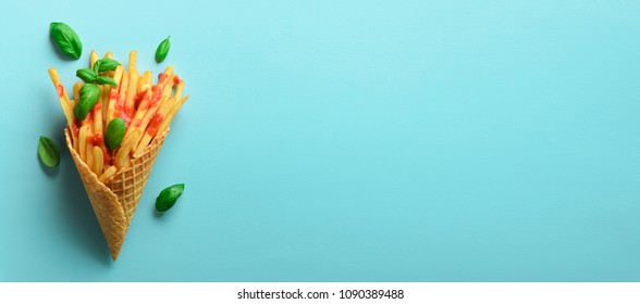 Fried potatoes in waffle cones on blue background. Hot salty french fries with sauce. Banner. Fast food, junk food, diet concept. Top view. Minimal style. Pop art design, creative concept.