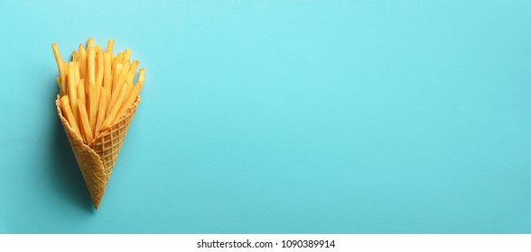 Fried potatoes in waffle cones on blue background. Hot salty french fries with tomato sauce. Fast food, junk food, diet concept. Top view. Minimal style. Pop art design, creative concept.
