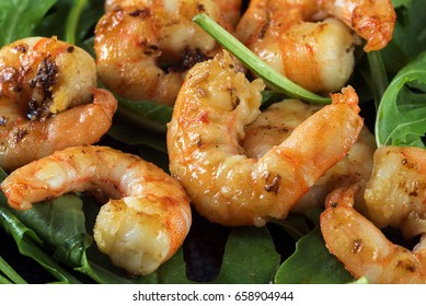 fried prawns or shrimps on arugula rocket salad, close up shot with selected focus, narrow depth of field