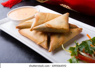 Fried prepared samosas served with sauce on a white plate