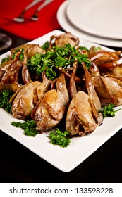 Fried quail with parsley on plate with black background