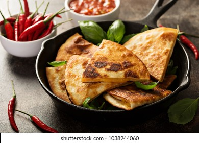 Fried quesadillas with cheddar cheese and hot pepper in a cast iron pan