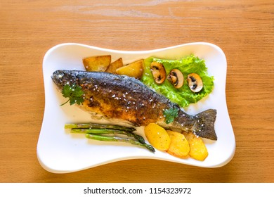 Fried rainbow trout served with vegetables and greens