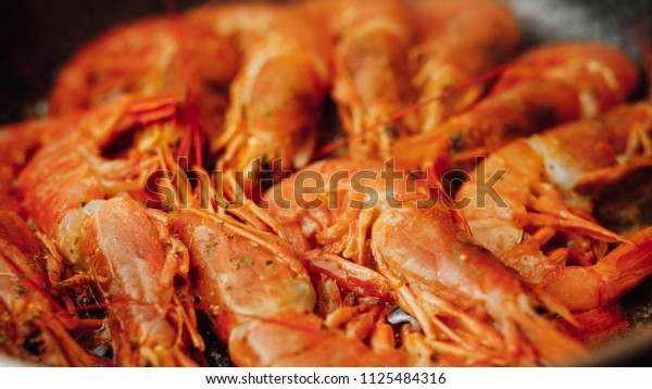 fried red shrimps with hot oil on pan