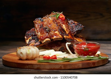 Fried ribs with rosemary, onion, sauce on a wooden round Board. Dark background. Place for text, copyspace