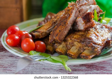 fried ribs with vegetables close up on the table