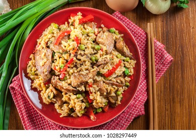 Fried rice with chicken and vegetables served on a plate. Popular chinese dish. Top view
