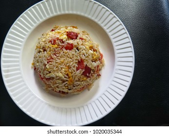 Fried rice with egg, bacon, tomatoes and fish sauce, olive oil, healthy delicious and popular Thai food for foreigner, white plate black isolated background, copy space, top view