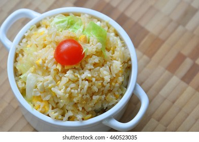 Fried rice with egg and red tomato on top in a white pot on wood plank