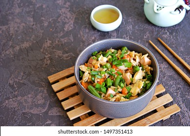 Fried rice with green green beans, carrots, egg and ham in a gray bowl on a dark brown concrete background. Selective focus. Asian food. Copy space.