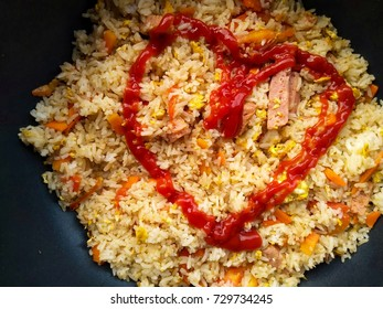 Fried rice with heart shape by tomato sauce. Love food concept.