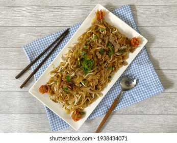 Fried Rice Noodle with smoked beef (Kwetiau Goreng Sapi - Indonesia) in a white plate on a wooden background. Top view. Copy space.