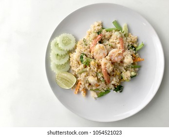 Fried rice with prawn herbs and vegetables served with lemon and cucumber in white plate on white background. Part of a series of nine Asian food dishes. Thai Food.