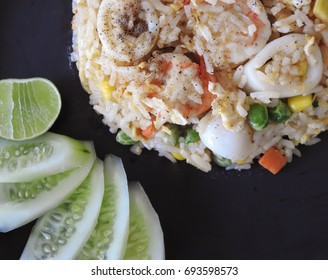 Fried rice and seafood with corns,carrots and beans decor by cucumbers and lemon sliced