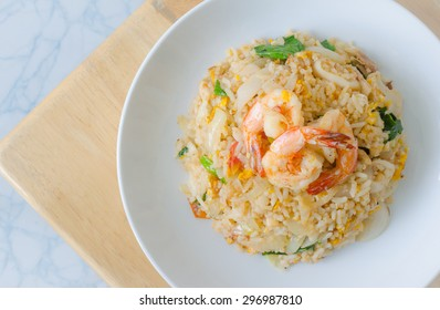 Fried rice with shrimp on the white dish on wooden table from top view