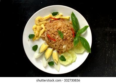 Fried rice with slice sausage served with hard boiled egg, shredded omelette and garnish with basil and oregano on wooden background