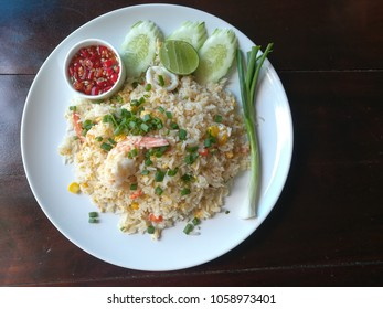 Fried rice stir fry with prawns and squids on wooden table.