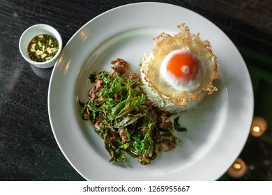 Fried rice with Thai Basil and fried egg  on white plate.