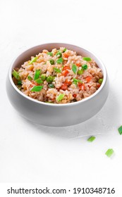 Fried rice with vegetables and egg in the gray ceramic bowl on the white table. Chinese food