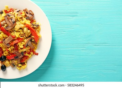 Fried rice with vegetables in plate on blue wooden table