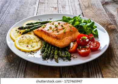 Fried salmon and asparagus on wooden table