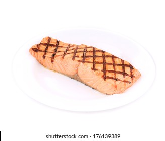 Fried salmon fillet on plate. Isolated on a white background.